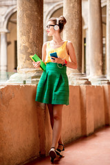 Young female student dressed casually with colorful books listening to the music during the break near the old university in Bologna city in Italy