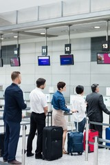 Passengers waiting in queue at a check-in counter with luggage