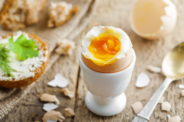 Perfect soft boiled egg, bread and butter for delicious healthy breakfast on a table. Traditional homemade food.