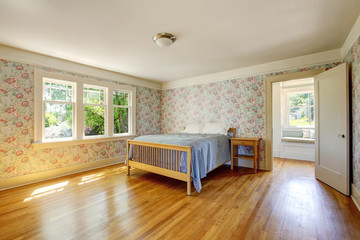 Bedroom interior with hardwood floor and vintage wallpaper walls.