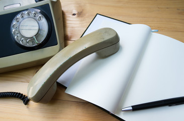 Notebook with a pencil eraser and put on wood antique phone.