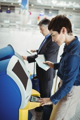 Business people using self service check-in machine