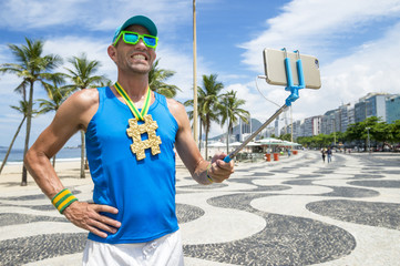 Hashtag gold medal athlete posing for a picture with his mobile phone on a selfie stick at Copacabana Beach in Rio de Janeiro, Brazil