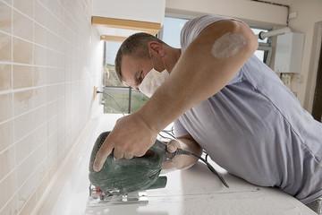 Man cutting kitchen countertop using electric jig saw.