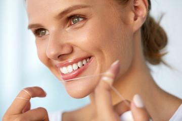 Dental Hygiene. Beautiful Woman Flossing Healthy White Teeth. High Resolution Image