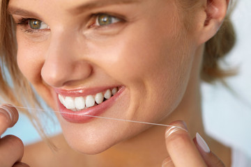 Dental Health. Woman With Beautiful Smile Flossing Healthy Teeth. High Resolution Image