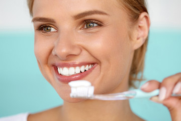 Beautiful Smiling Woman Brushing Healthy White Teeth With Brush. High Resolution Image
