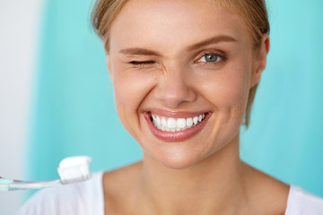 Woman With Beautiful Smile Brushing Healthy White Teeth. High Resolution Image