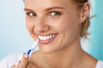 Healthy White Teeth. Beautiful Smiling Woman Using Whitening Pen. High Resolution Image