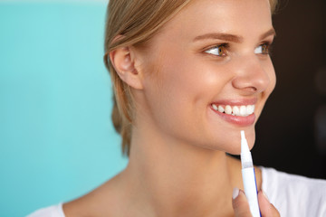 Woman With Beautiful Smile, Healthy Teeth Using Whitening Pen. High Resolution Image