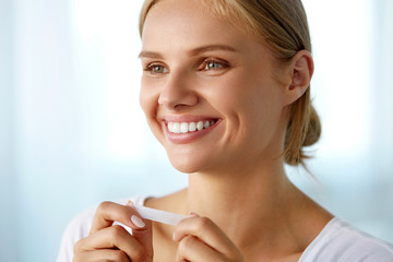 Woman Using Teeth Whitening Strip For Beautiful White Smile. High Resolution Image