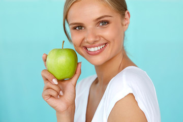Smiling Woman With Beautiful Smile, White Teeth Holding Apple. High Resolution Image