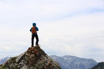 successful woman backpacker hiking on mountain peak cliff Wall mural