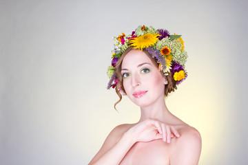 Милая девушка с венком на голове из живых цветов.