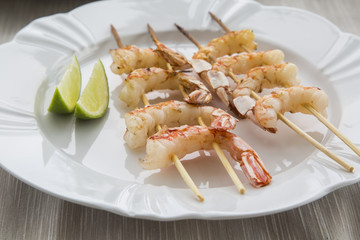 Fried shrimp with lemon on a white plate oven old wooden backgro