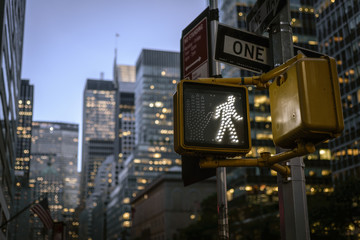 NYC crosswalk sign on busy one way street with sunset skyline in the background.