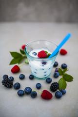 Yogurt with fresh berries fruit on light background.