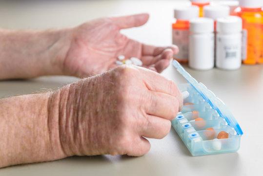 Elderly man sorting daily medication into a pill box.