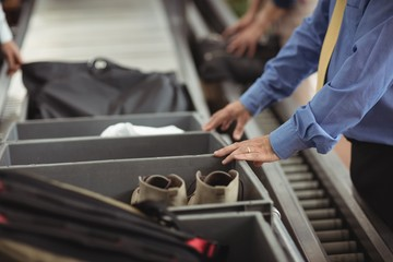 Man putting shoes into tray for security check