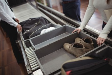 Woman putting shoes into tray for security check