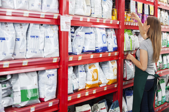 Saleswoman Arranging Food Packages In Pet Store