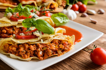 Pancakes stuffed with Bolognese filling - minced beef, pepper, onion, garlic and basil with tomato sauce