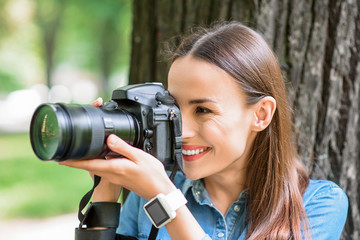 Cheerful young woman photographing in park