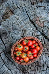 Cherry tomatoes in a small basket on an old wooden surface with copyspace, flat lay