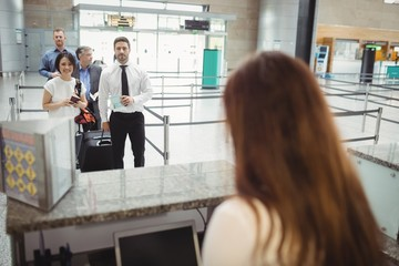 Passengers waiting in queue at check-in counter
