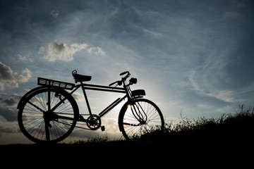 silhouette of a retro bicycle. parked in a meadow in evening, th