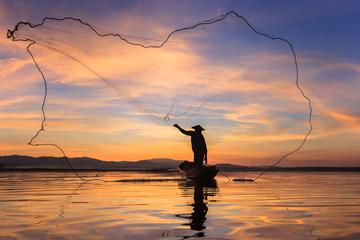 Fisherman silhouette on boat.