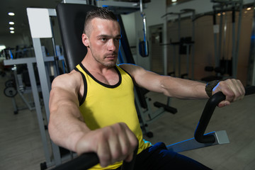 Man Training Chest Exercises On A Machine
