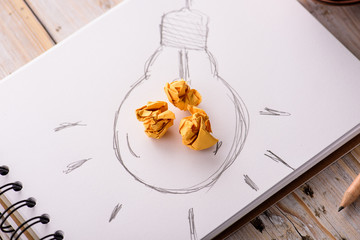 Inspiration concept crumpled paper with light bulb metaphor for