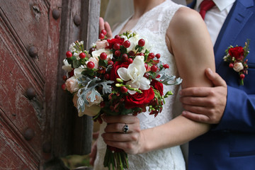 wedding bouquet in hands of bride against the background of vint