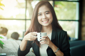 Asian business woman is working and drinking coffee and business