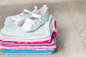 Folded pink and white bodysuit with shoes on it on grey wooden background. diaper for newborn girl. Stack of infant clothing. Child outfit. Copy space.