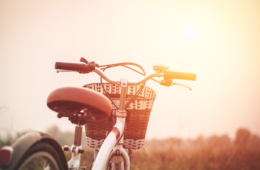 beautiful landscape image with vintage Bicycle at sunset ; vinta