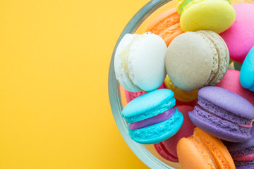 Colorful macarons on yellow background
