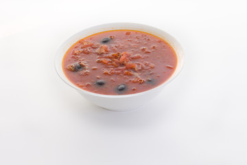 red soup with black olives on a white table