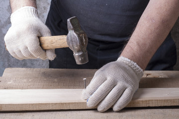 Carpenter working with plane on wooden background at Building Site. workplace