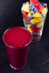 Blueberry, mango and grapefruit smoothie  on black background
