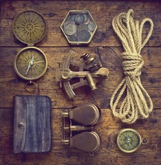 Fototapete - Overhead view of pirate or sailor gear laid out for a backpacking trip on a old wood floor. Items include, rope, compass, money, binoculars, sextant , shell. Stories background.