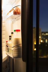 door of refrigerator with milk bottles in night