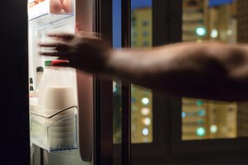 hand reaches for milk bottle in fridge in night