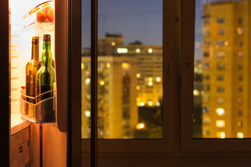 Open refrigerator with bottles in night