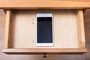 Fototapeta mobile phone in open drawer obraz