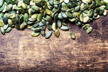 ..Pumpkin seeds over wood background with copy space .