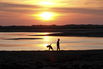 Couple silhouetted against an orange sky on the coast at sunset
