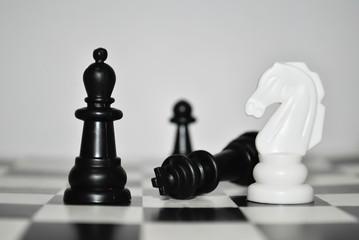 Шах и мат/ Шахматные фигуры на шахматном поле, классические черные и белые