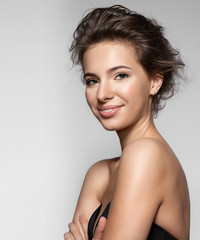 Smiling girl with natural make-up, clean skin and white teeth on grey background
